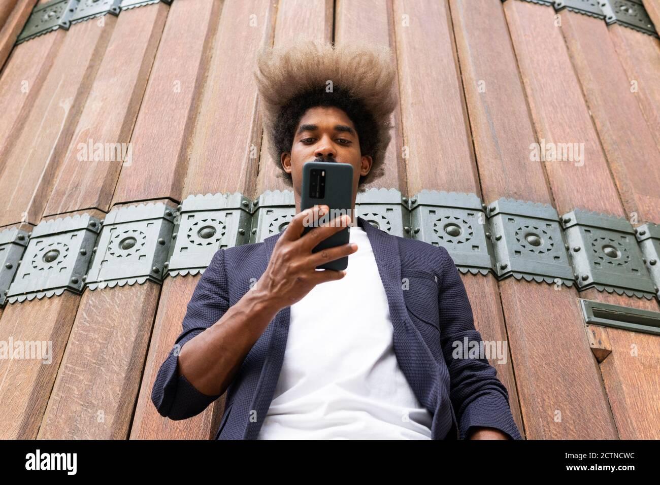 Desde abajo de un hombre africano en traje usando el suyo teléfono móvil frente a una pared de madera Foto de stock