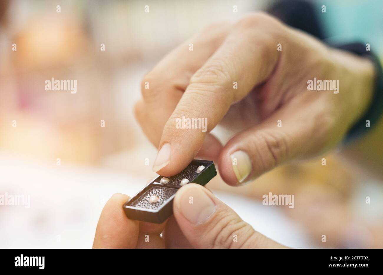primer plano mano toque dominó abultamiento juego estrategia de mano para ciegos Foto de stock