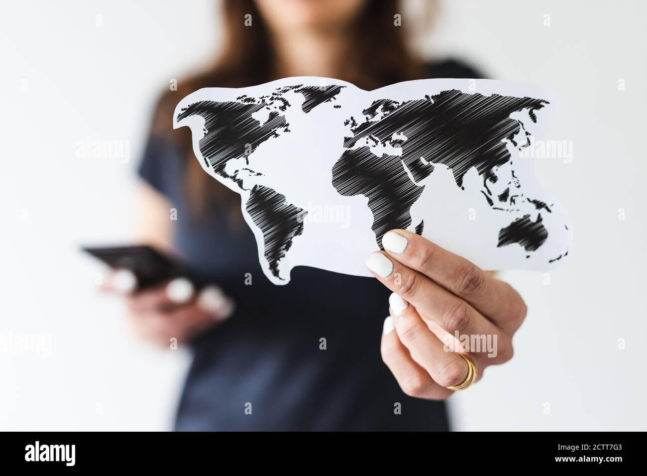 concepto de comercio mundial o viajes internacionales, mujer que sostiene el mapa del mundo hacia la cámara mientras navega algo en su smartphone filmado en shal Foto de stock