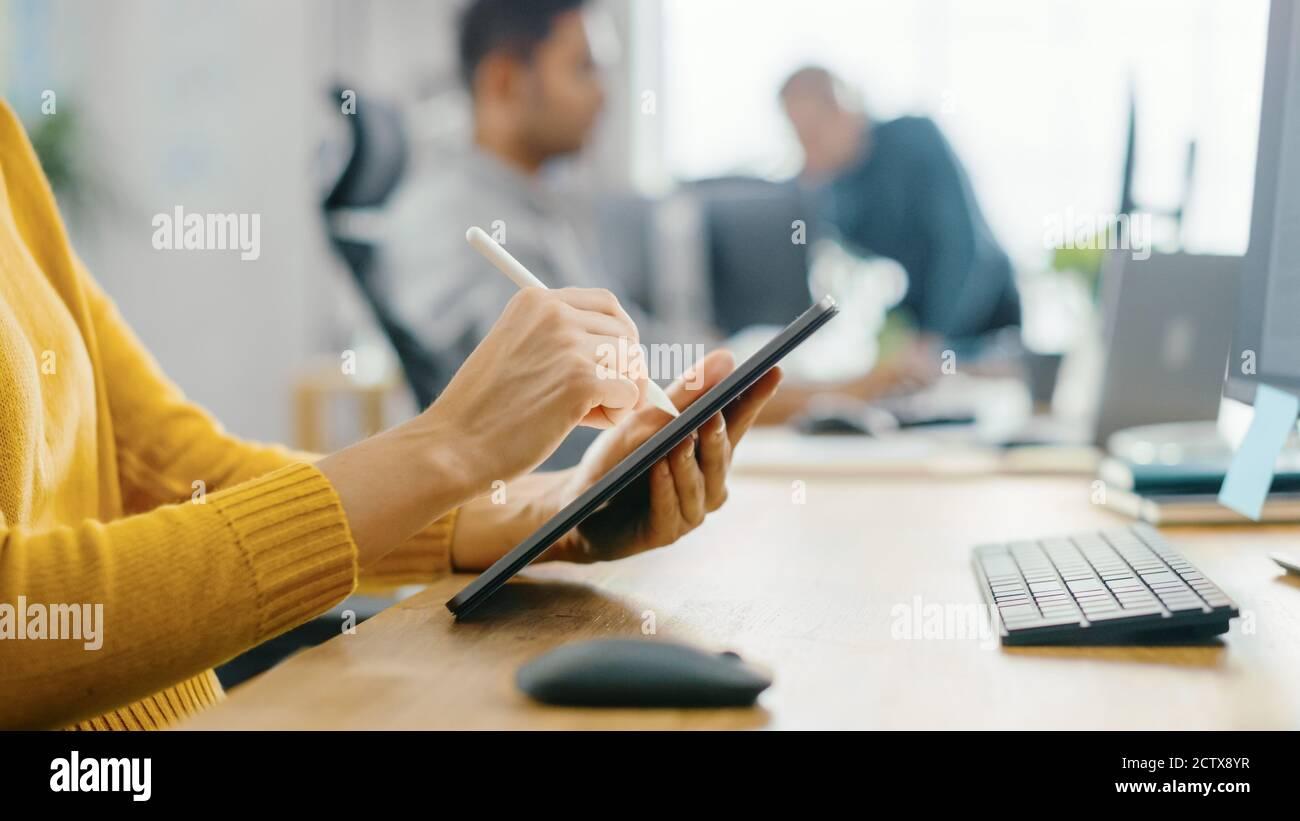 Mujer joven anónima sentada en su escritorio ella está dibujar, escribiendo y usando el lápiz con la computadora de la tableta digital. Céntrese en las manos con Pen. Oficina Bright Foto de stock