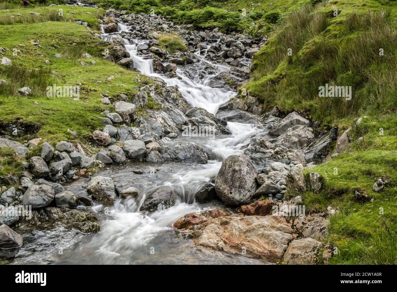 Uno de los varios arroyos que caen por la orilla de la calle Kirkstone Pass. Cerca de la carretera como se baja a Brotherswater y Ullswater. Foto de stock