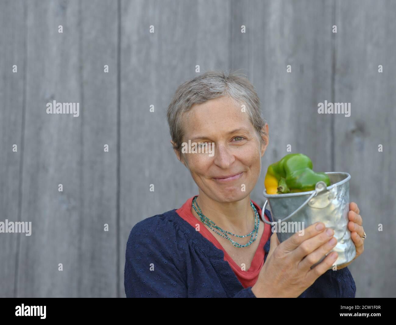 Mujer caucásica canadiense moderna de mediana edad con pelo corto muestra un pequeño cubo lleno de pimientos orgánicos grandes de origen casero. Foto de stock