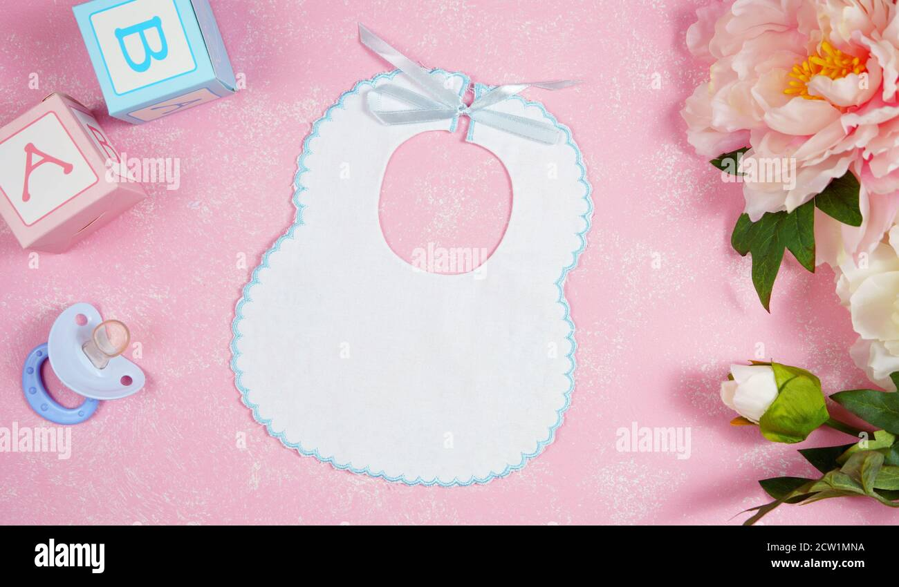 Bebé babero ropa de vivero mamá bloggers escritorio mocazas con peonie flotadores sobre fondo con textura rosa. Arriba ver el encabezado del héroe del blog composición creativa Foto de stock