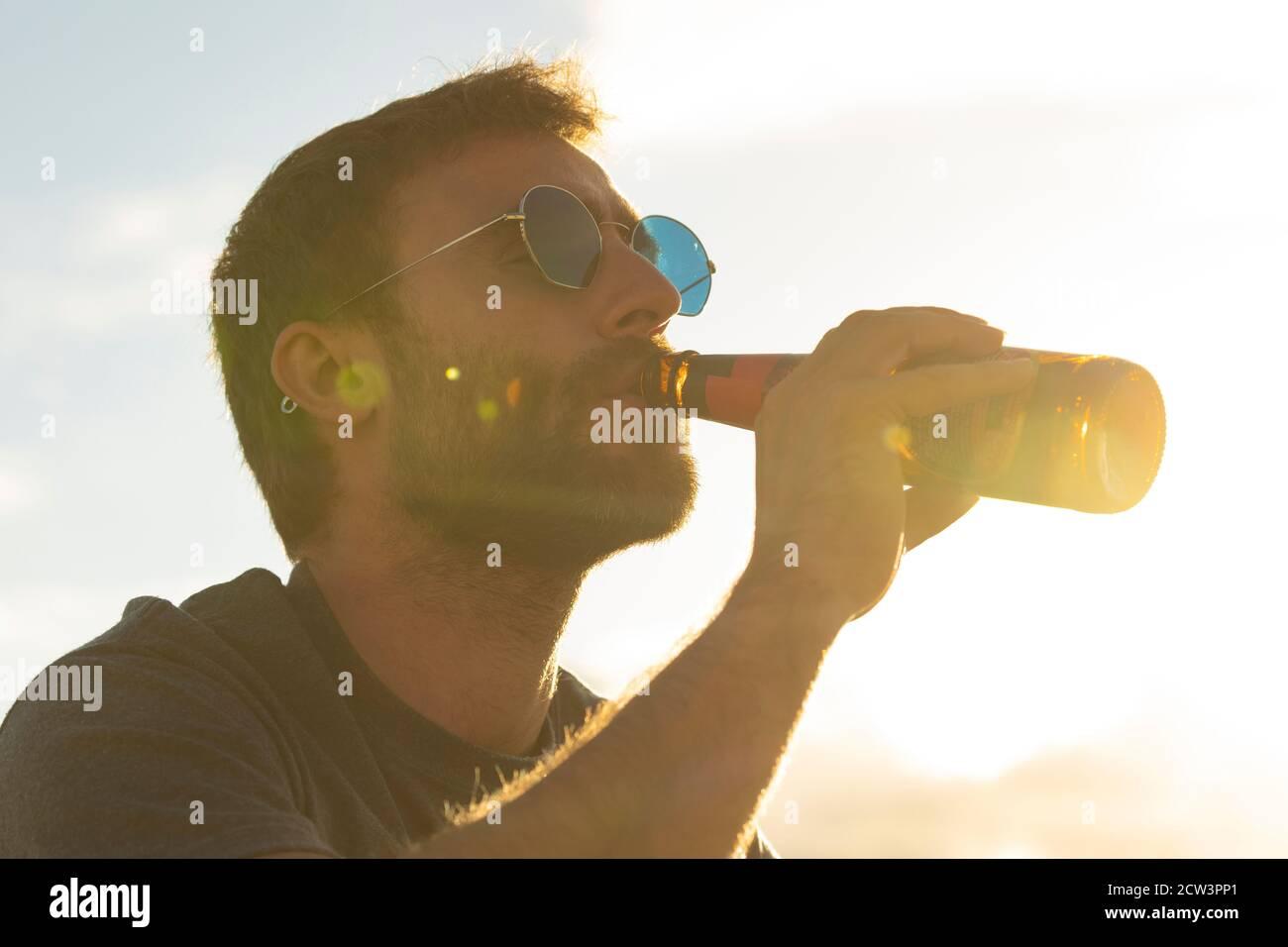 Un joven, con vasos y barba, bebe cerveza de una botella, mientras disfruta del paisaje y la puesta de sol, en Galicia, al norte de España. Foto de stock