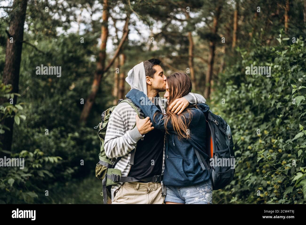 Pareja joven con mochilas en la espalda sonriendo y caminando por el bosque, disfrutar del paseo. Foto de stock