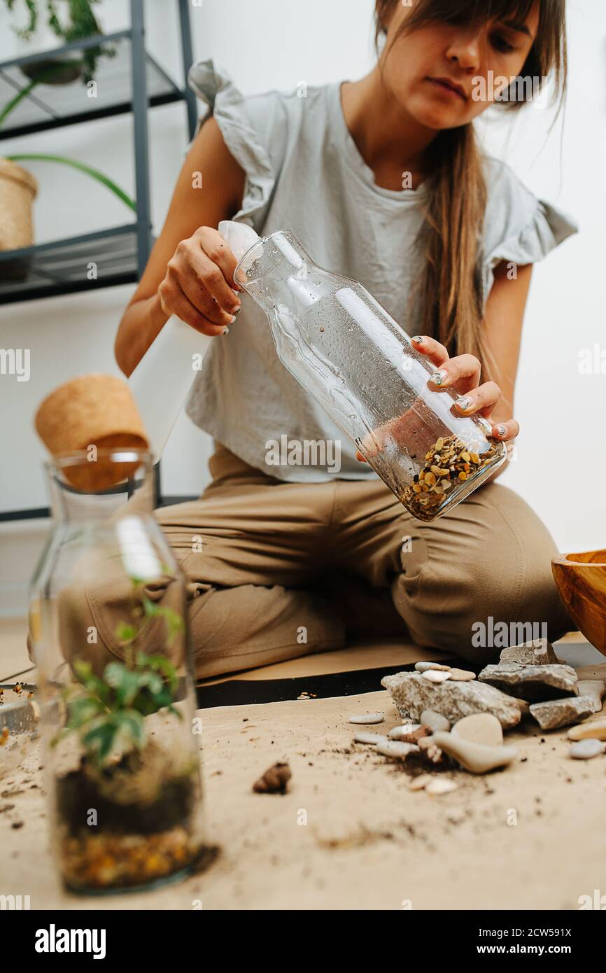 Mujer en el salón, rociando botella de vidrio con arcilla artificial en el fondo Foto de stock