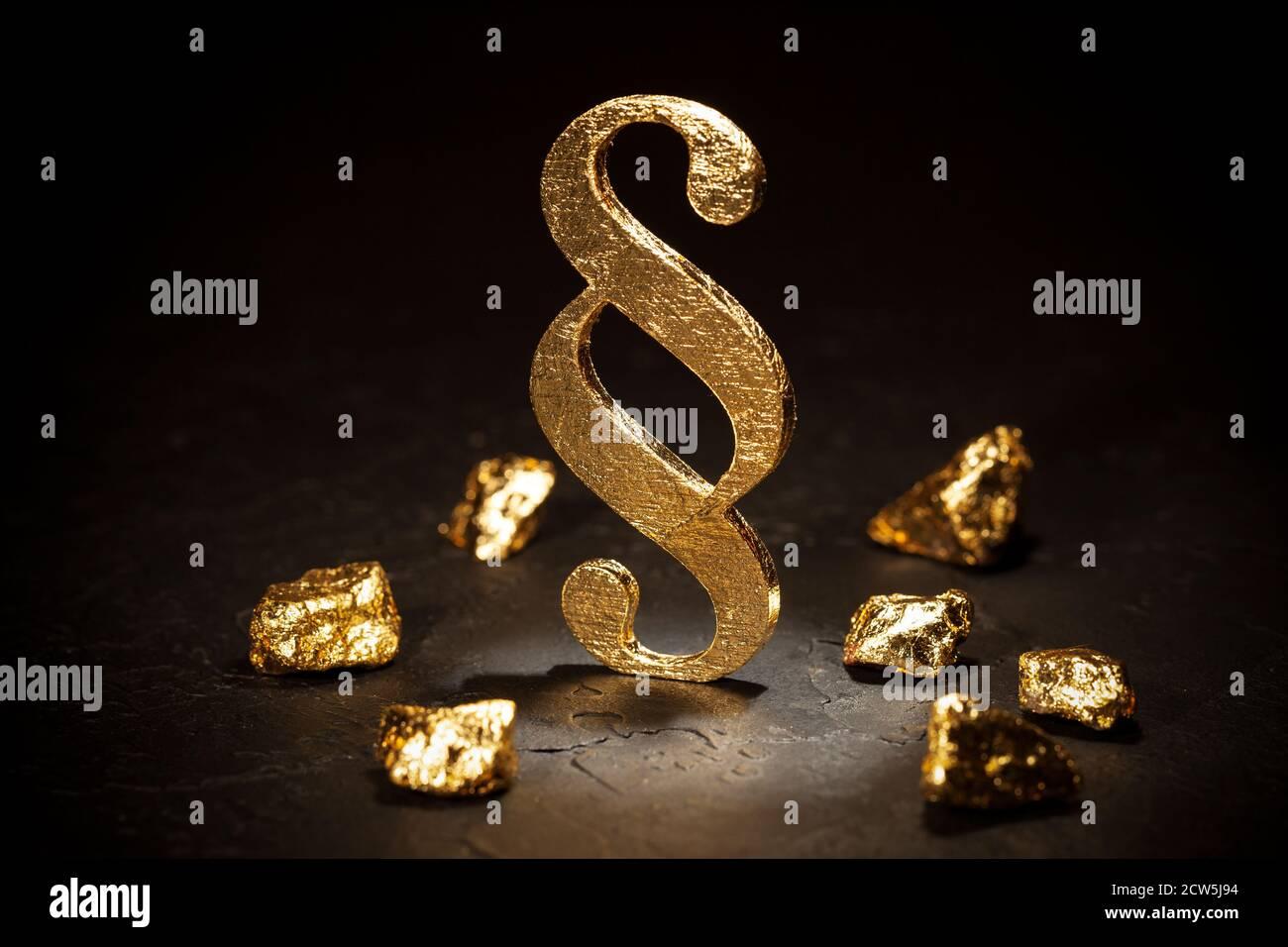 Signo de párrafo de oro y pepitas de oro sobre fondo negro. Foto de stock
