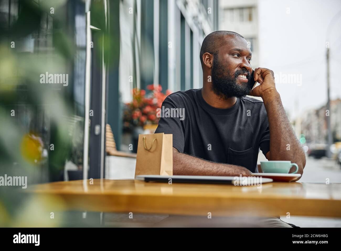 Hombre contento disfrutando de una agradable charla telefónica en la ciudad Foto de stock