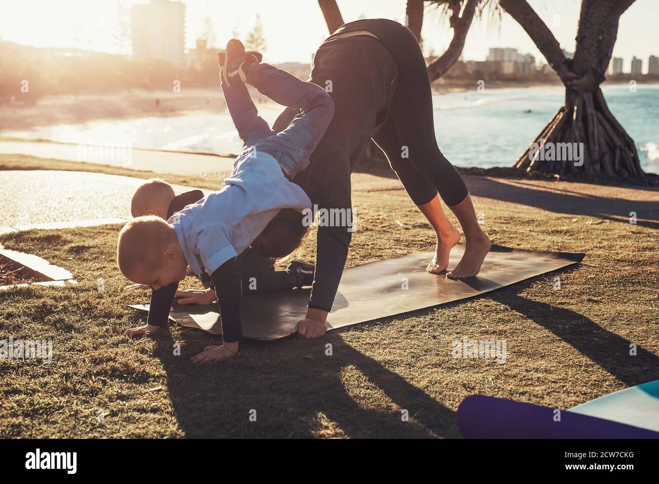 Madre joven y dos hijos haciendo gimnasia y estirándose en el parque de la ciudad al atardecer con vista al océano. Mujer en yoga asana y niño en su espalda Foto de stock