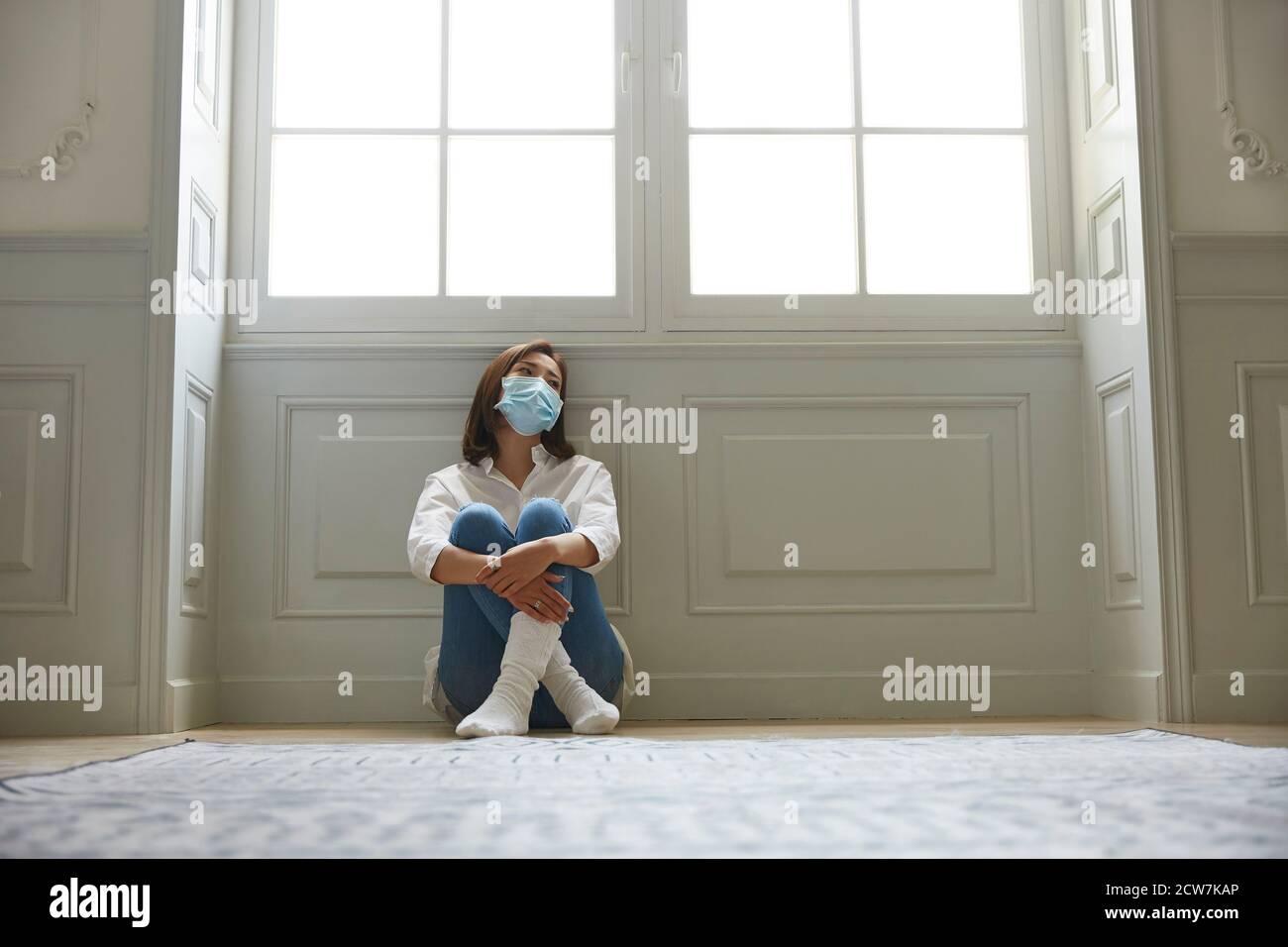 mujer asiática joven en cuarentena en casa usando máscara facial sentado en las piernas del piso se cruzó con un aspecto triste y deprimido Foto de stock