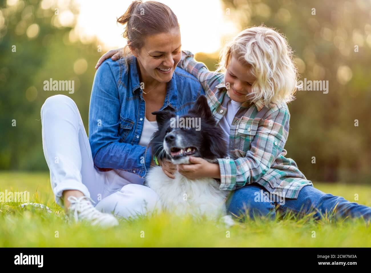 Feliz madre e hijo al aire libre acariciando a su perro Foto de stock