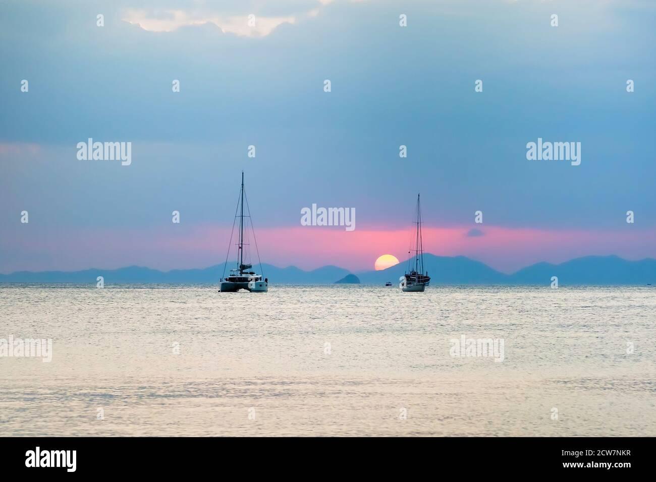 Tres veleros en el mar. Durante el atardecer, el sol se pone sobre las montañas. Foto de stock