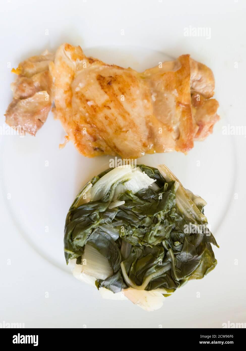 Pollo a la parrilla con garnished con acelga. Una comida ideal para seguir una dieta saludable y equilibrada Foto de stock