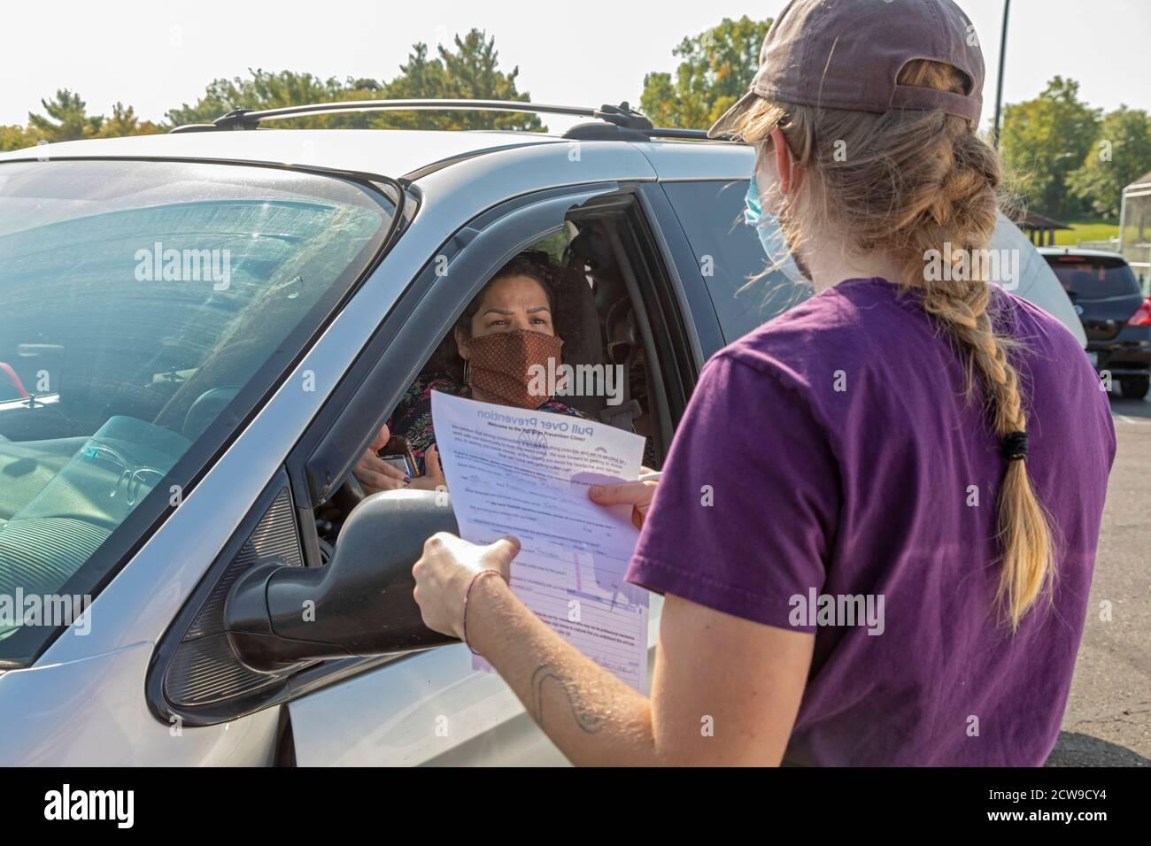 Ypsilanti, Michigan - UNA mujer explicó lo que las reparaciones de su coche necesita como profesional y amateur mecánicos de automóviles hizo reparaciones gratis en un Pull Over Prevent Foto de stock