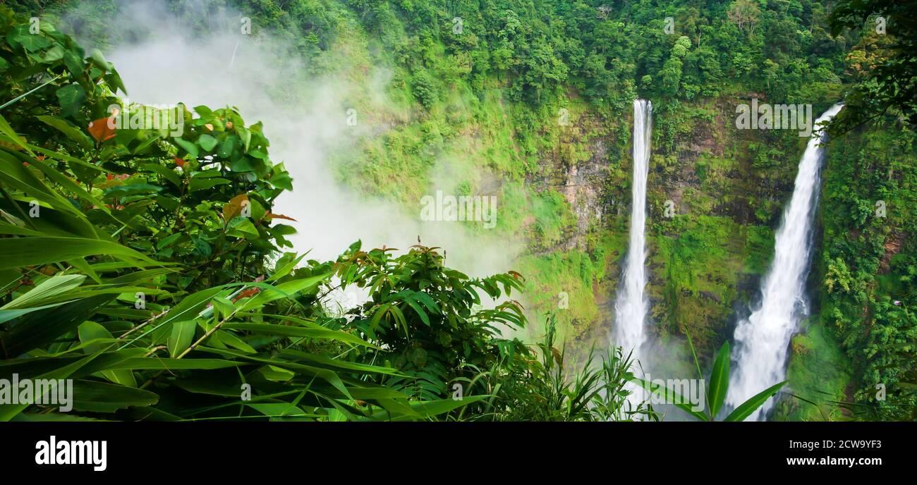 Paisaje Tad Fane cascada en la niebla, hermosa cascada gemela en temporada de lluvia, atracciones turísticas en el sur de Laos. Foto de stock
