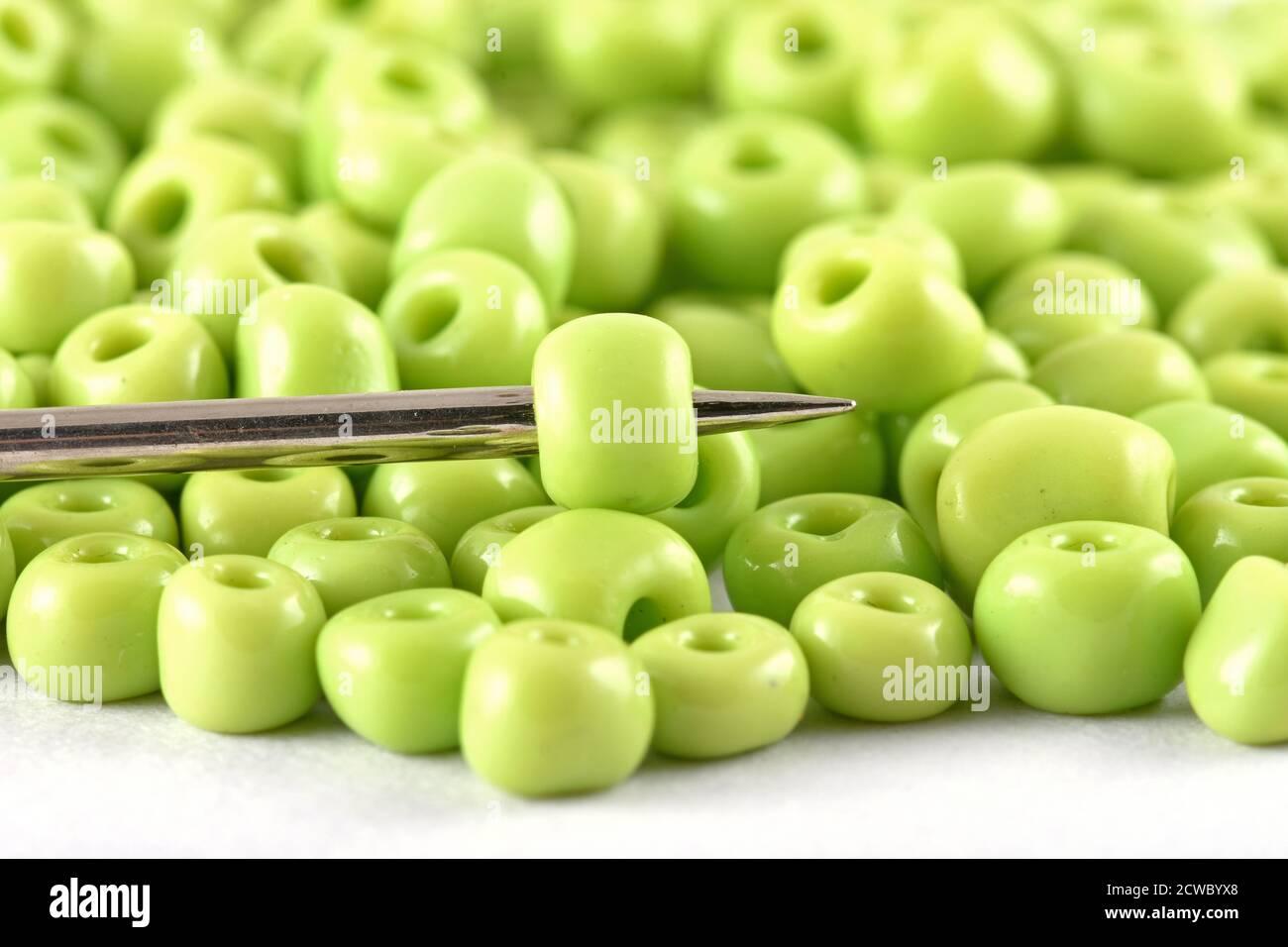 Las perlas se extienden sobre fondo blanco con aguja. Cuentas con aguja . Close up, macro, se utiliza en el acabado de la ropa de moda. Hacer collar de cuentas, cuentas f Foto de stock