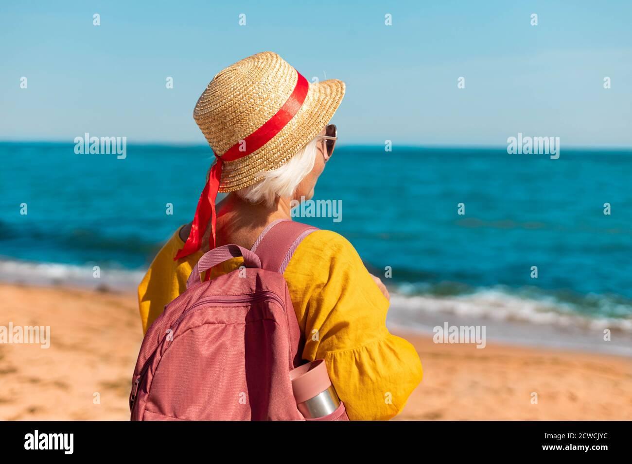 Retrato de una joven feliz en un pajizo de verano sombrero y gafas con mochila turística y termo disfrute de la hermosa vista al mar Foto de stock