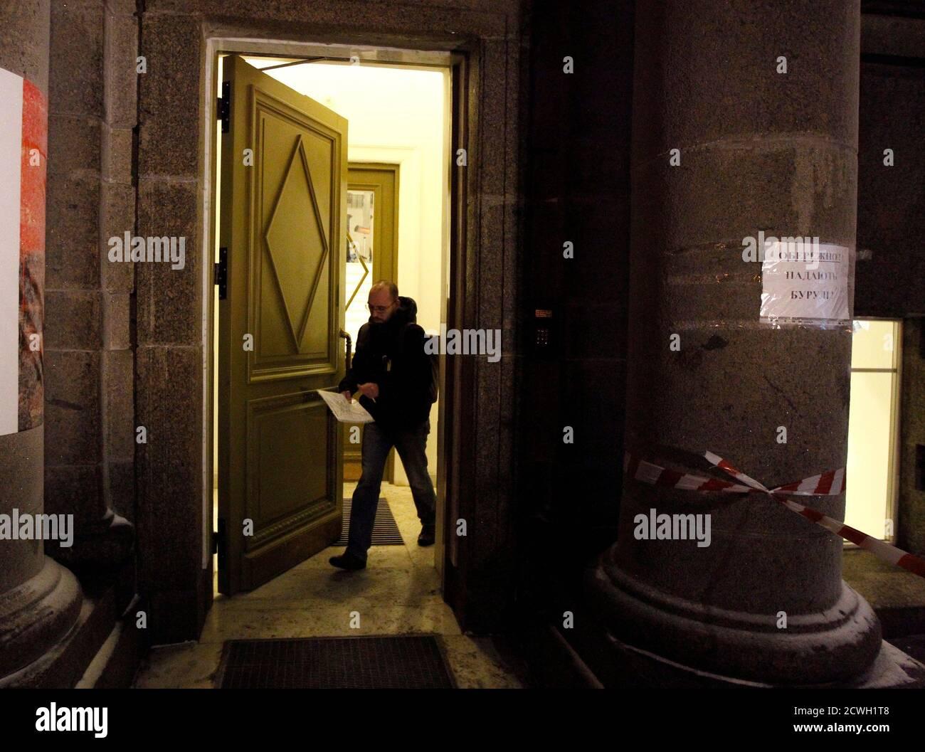 Igor Skliarevsky sale de su oficina en Kiev, 12 de diciembre de 2013. De día, Igor Skliarevsky trabaja como diseñador gráfico. Por la noche, es un manifestante anti-gubernamental, a veces manejando las barricadas en la capital nevada de Ucrania. El joven de 36 años entrega mapas para los compañeros manifestantes, dirigiéndolos a puestos médicos o cocinas. También creó un sitio web que coordinaba alimentos, ropa de abrigo y otros suministros para los acampados en la Plaza de la Independencia de Kiev. Foto tomada el 12 de diciembre de 2013. REUTERS/Vasily Fedosenko (UCRANIA - Tags: POLÍTICA DISTURBIOS CIVILES) Foto de stock