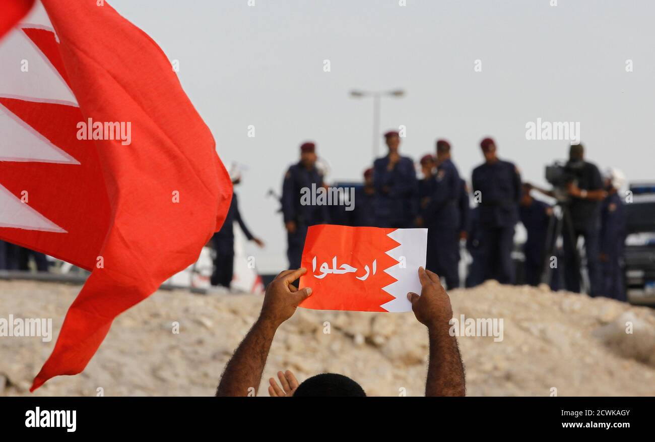 """An anti-government protester holds up a poster of a Bahraini flag that reads """"leave"""" in front of riot police during a protest held in Riffa, south of Manama, March 11, 2011. Bahraini police blocked several thousand protesters from reaching the royal palace on Friday, amid fears the march would spark fighting on a Gulf island where the majority is Shi'ite Muslim but the ruling family is Sunni. REUTERS/Hamad I Mohammed (BAHRAIN - Tags: POLITICS CIVIL UNREST) Foto de stock"""