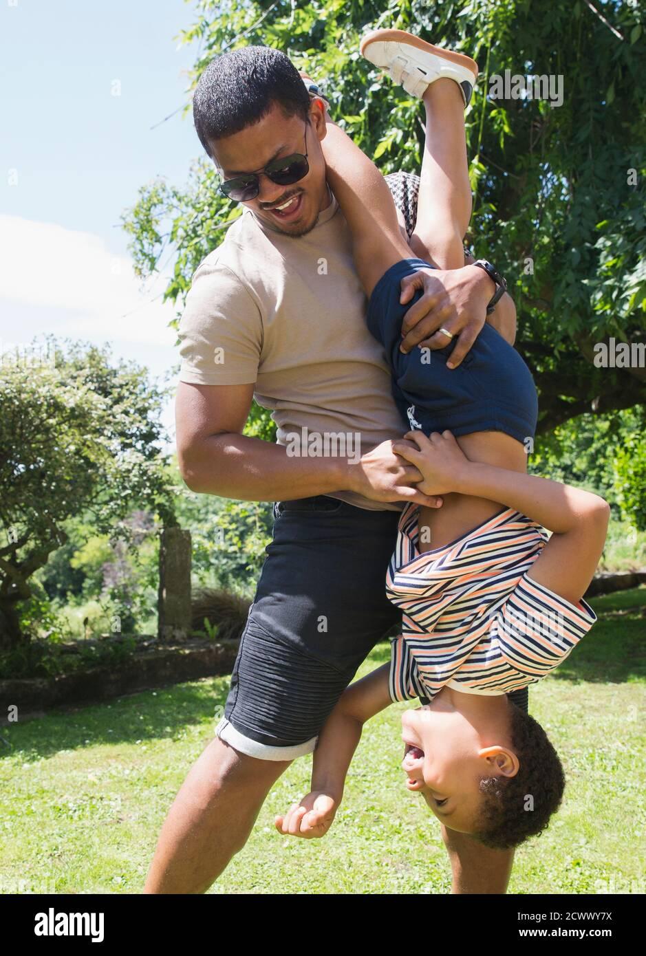 Padre juguetón sosteniendo al hijo al revés en el soleado patio trasero de verano Foto de stock