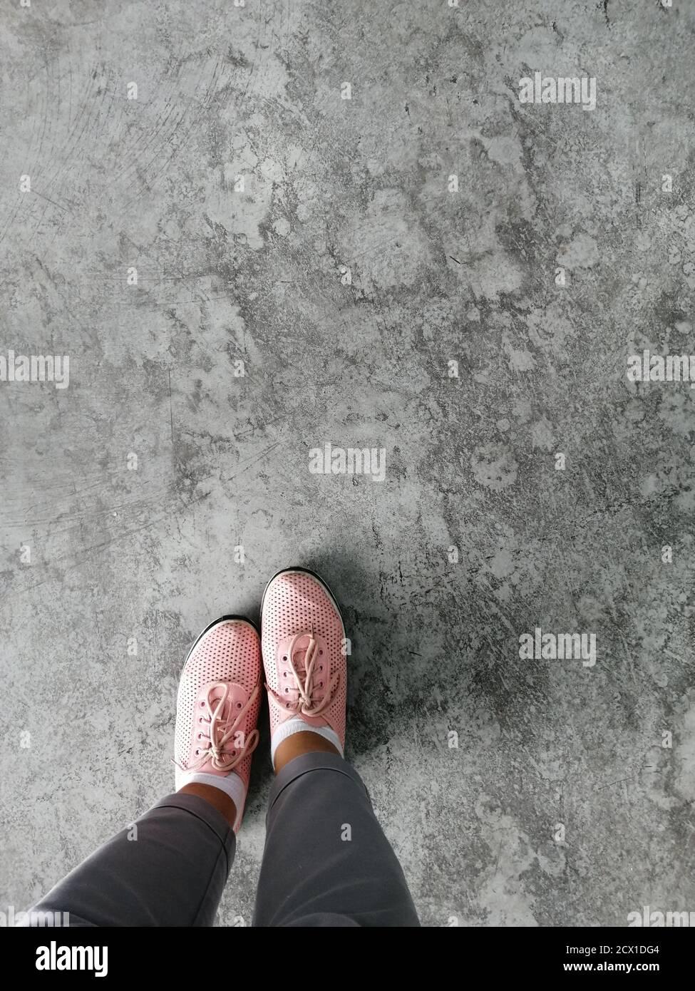 Vista superior viejo tono marrón piel zapato detalle en piso de concreto grunge, pies selfie usando zapatos de sneakers en el piso. Foto de stock