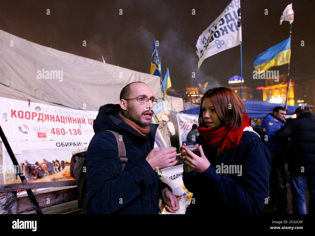 Igor Skliarevsky and his wife Elena drink tea in a pro-European protesters camp at Independence Square in Kiev, December 16, 2013. By day, Igor Skliarevsky works as a graphic designer. By night, he is an anti-government protester, sometimes manning the barricades in Ukraine's snowy capital. The 36-year-old delivers maps for fellow protesters, directing them to medical posts or kitchens. He also set up a website coordinating food, warm clothing and other supplies for those camped out on Kiev's Independence Square. Picture taken December 16, 2013.  REUTERS/Vasily Fedosenko (UKRAINE - Tags: POLIT Foto de stock