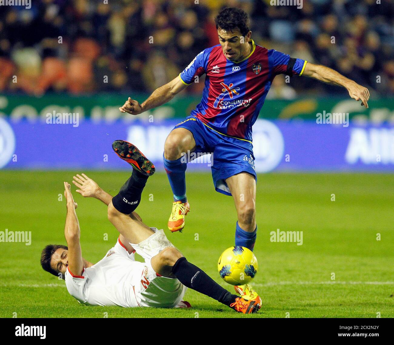 Levante's Xavi Venta controls the ball over Sevilla's Manu del Moral (on ground) during their Spanish first division soccer match at the Ciudad de Valencia Stadium in Valencia December 10, 2011. REUTERS/Heino Kalis (SPAIN - Tags: SPORT SOCCER) Foto de stock