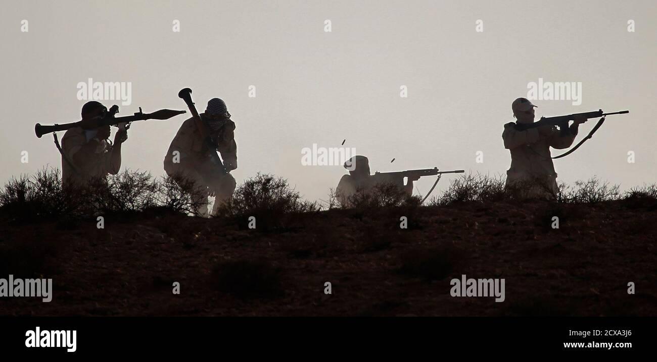 Los combatientes rebeldes libios con la Brigada Revolucionaria de Trípoli toman parte en un ejercicio de fuego en vivo durante un evento de graduación cerca de Nalut en el oeste de Libia, el 6 de agosto de 2011. REUTERS/Bob Strong (LIBIA - Tags: CONFLICTO POLÍTICO) Foto de stock