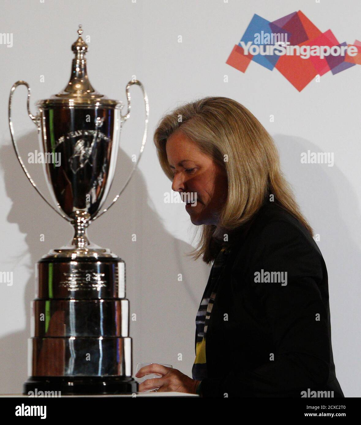 Stacey Allaster, Chairman and Chief Executive Officer of the Women's Tennis Association (WTA), walks past the Billie Jean King trophy during a WTA announcement in Singapore May 8, 2013. From left is Singapore Sports Council's CEO Lim Teck Yin, World Sports Group's Chief Operating Officer Andrew Georgiou and Singapore Tourism Board's CEO Lionel Yeo. Singapore will host the glittering annual finale of the women's tennis season from 2014 until 2018, the WTA said on Wednesday.  REUTERS/Edgar Su (SINGAPORE - Tags: SPORT TENNIS) Foto de stock