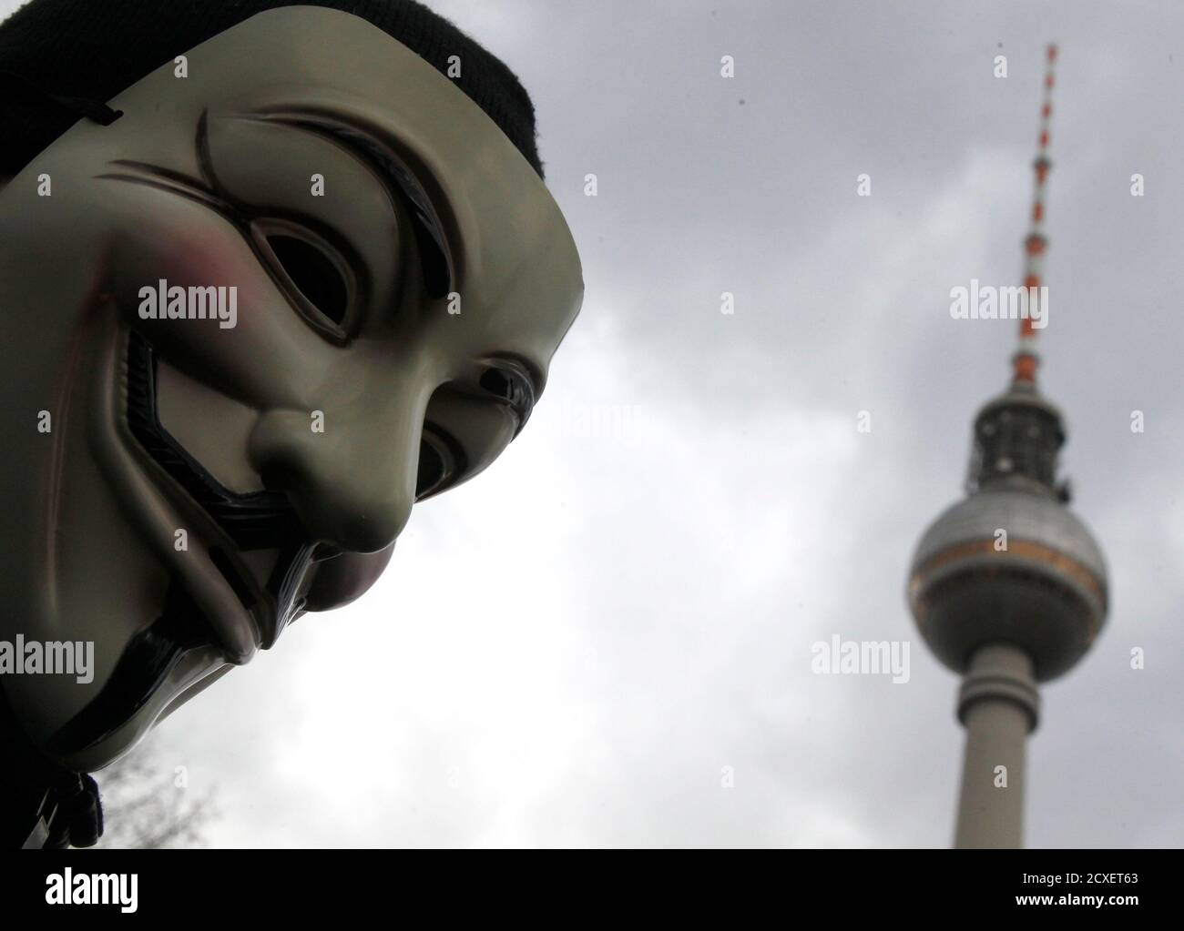 A protestor wearing Guy Fawkes masks participates in a demonstration next to the television tower against the Anti-Counterfeiting Trade Agreement (ACTA) in Berlin February 25, 2012. Protesters fear that ACTA, which aims to cut trademark theft and other online piracy, will curtail freedom of expression, curb their freedom to download movies and music for free and encourage Internet surveillance. REUTERS/Tobias Schwarz (GERMANY - Tags: POLITICS CIVIL UNREST) Foto de stock