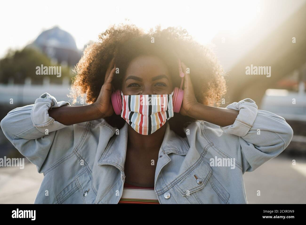 Chica negra escuchando música con auriculares mientras lleva máscara Exterior - concepto de estilo de vida Coronavirus Foto de stock