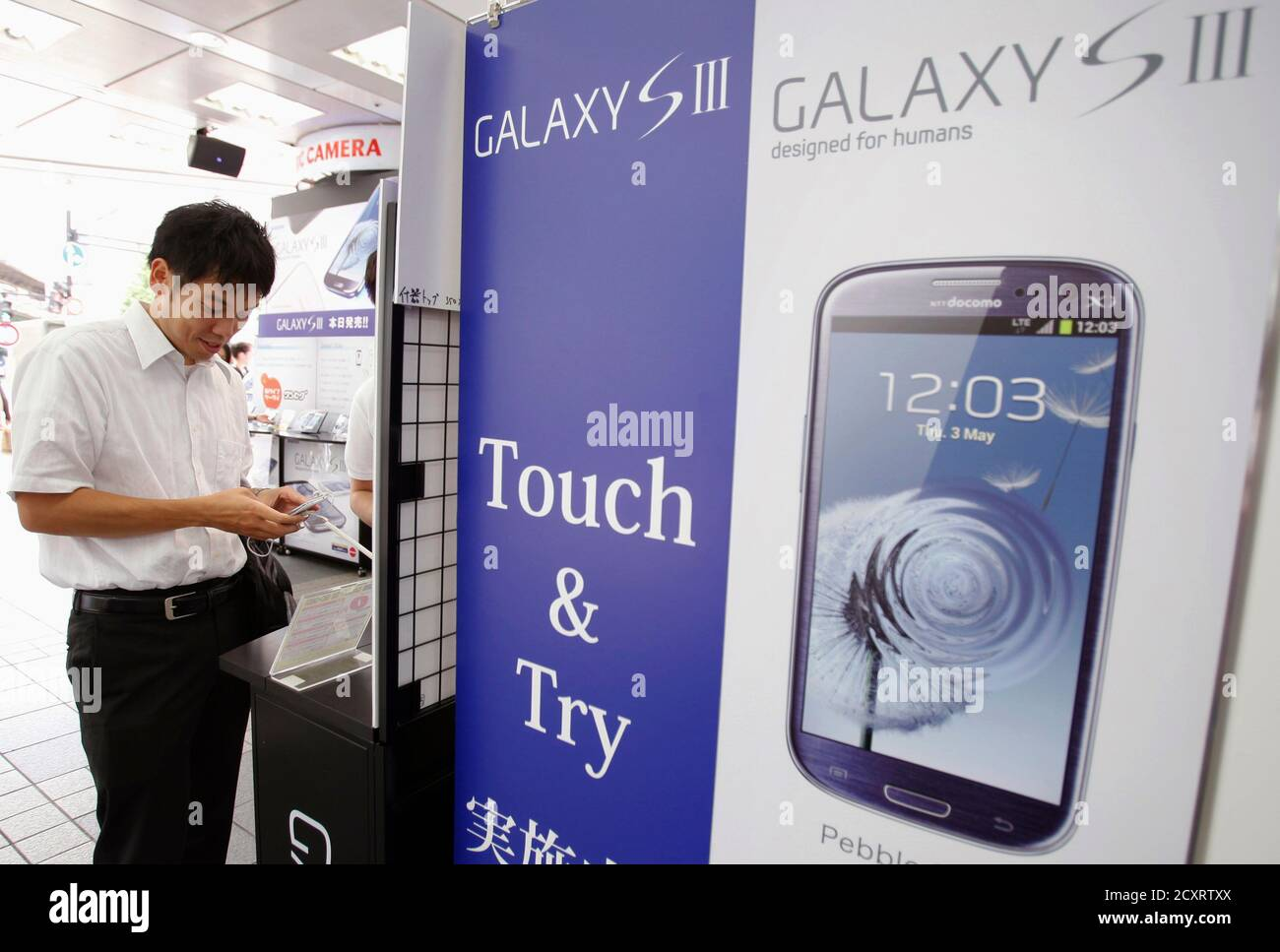 Un cliente prueba un smartphone Galaxy S III de Samsung, lanzado por el mayor operador móvil de Japón NTT Docomo Inc, en una tienda de electrónica en Tokio el 28 de junio de 2012. El Galaxy S III ha recibido las críticas más positivas entre cualquiera de los smartphones Samsung, y el gigante de la tecnología dice que el teléfono está en camino de convertirse en su teléfono inteligente más rápido de venta, con las ventas probablemente a los 10 millones en los primeros dos meses desde su lanzamiento. REUTERS/Yuriko Nakao (JAPÓN - Tags: TECNOLOGÍA DE LAS CIENCIAS EMPRESARIALES) Foto de stock
