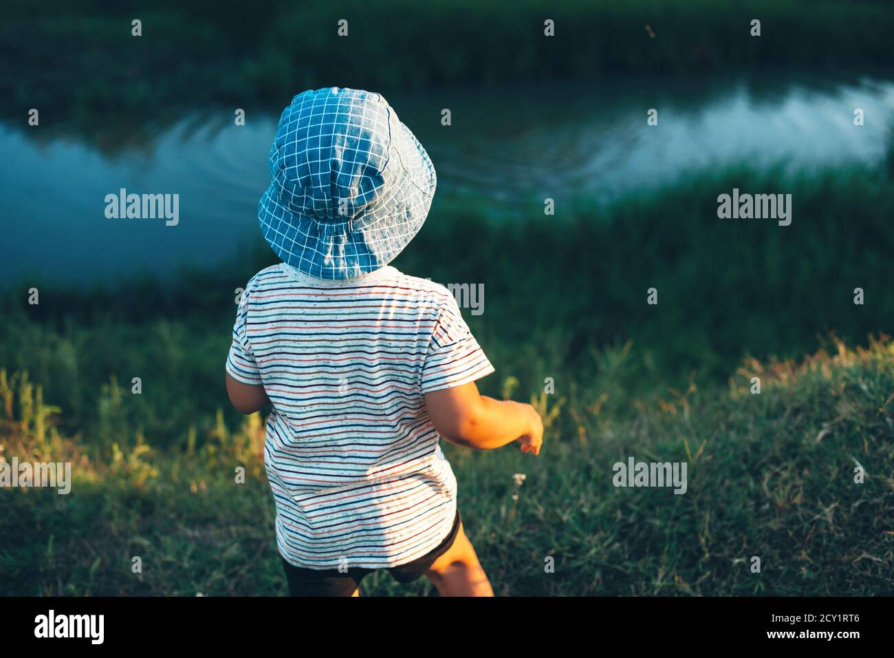 Niño caucásico mirando un pequeño río y lanzando piedras usando un sombrero azul en un campo verde Foto de stock