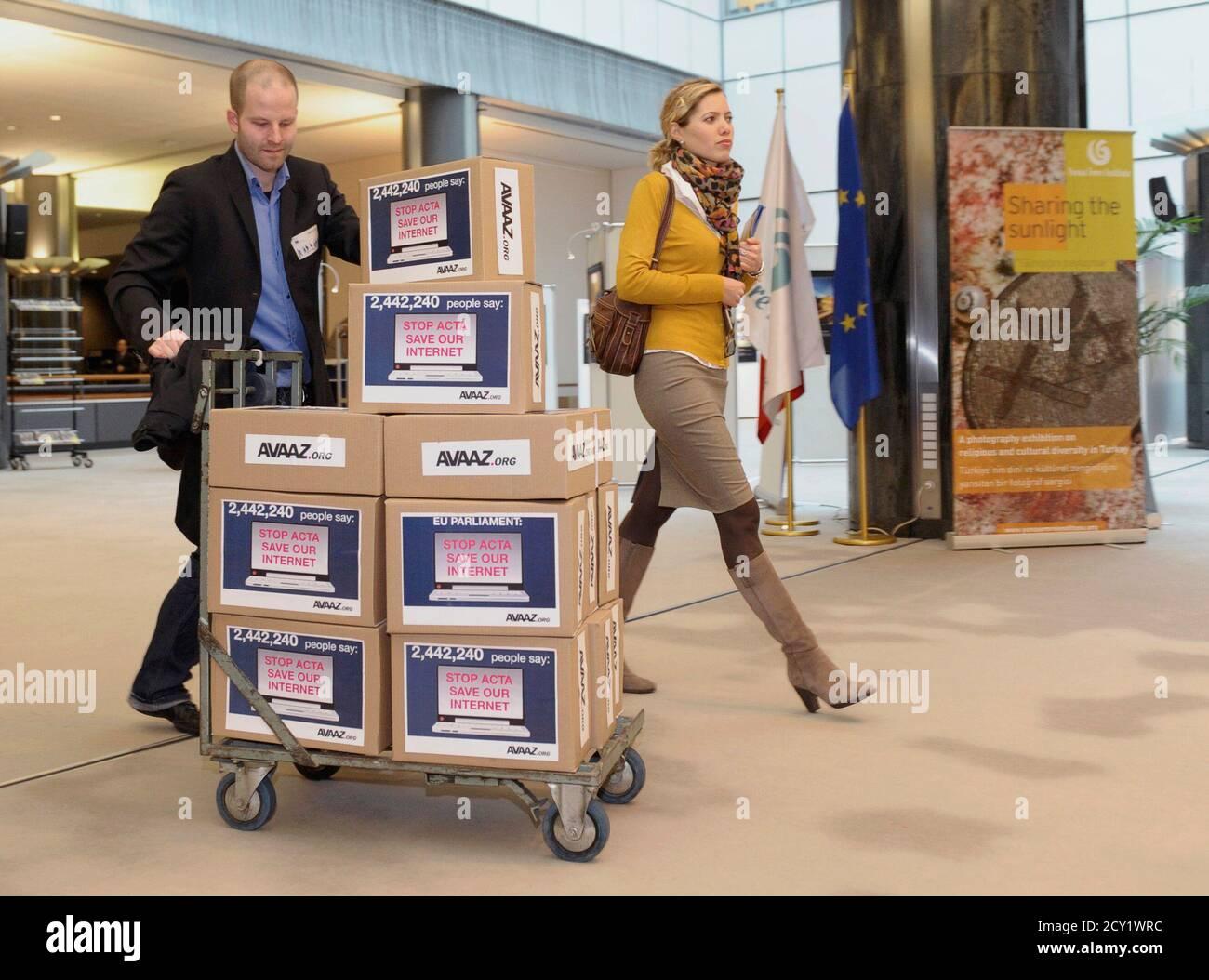 Miembros del grupo de Avaaz.org activistas traen cajas que simbolizan 2,442,240 firmas de una petición contra el ACTA (Acuerdo Comercial Antifalsificación) al Parlamento Europeo en Bruselas el 28 de febrero de 2012. Avaaz.org el temor de que el ACTA, que pretende reducir el robo de marcas comerciales y otras actividades de piratería en línea, reducirá la libertad de expresión, frenará su libertad de descargar películas y música de forma gratuita y fomentará la vigilancia en Internet. REUTERS/Eric Vidal (BÉLGICA - Tags: SOCIEDAD POLÍTICA) Foto de stock