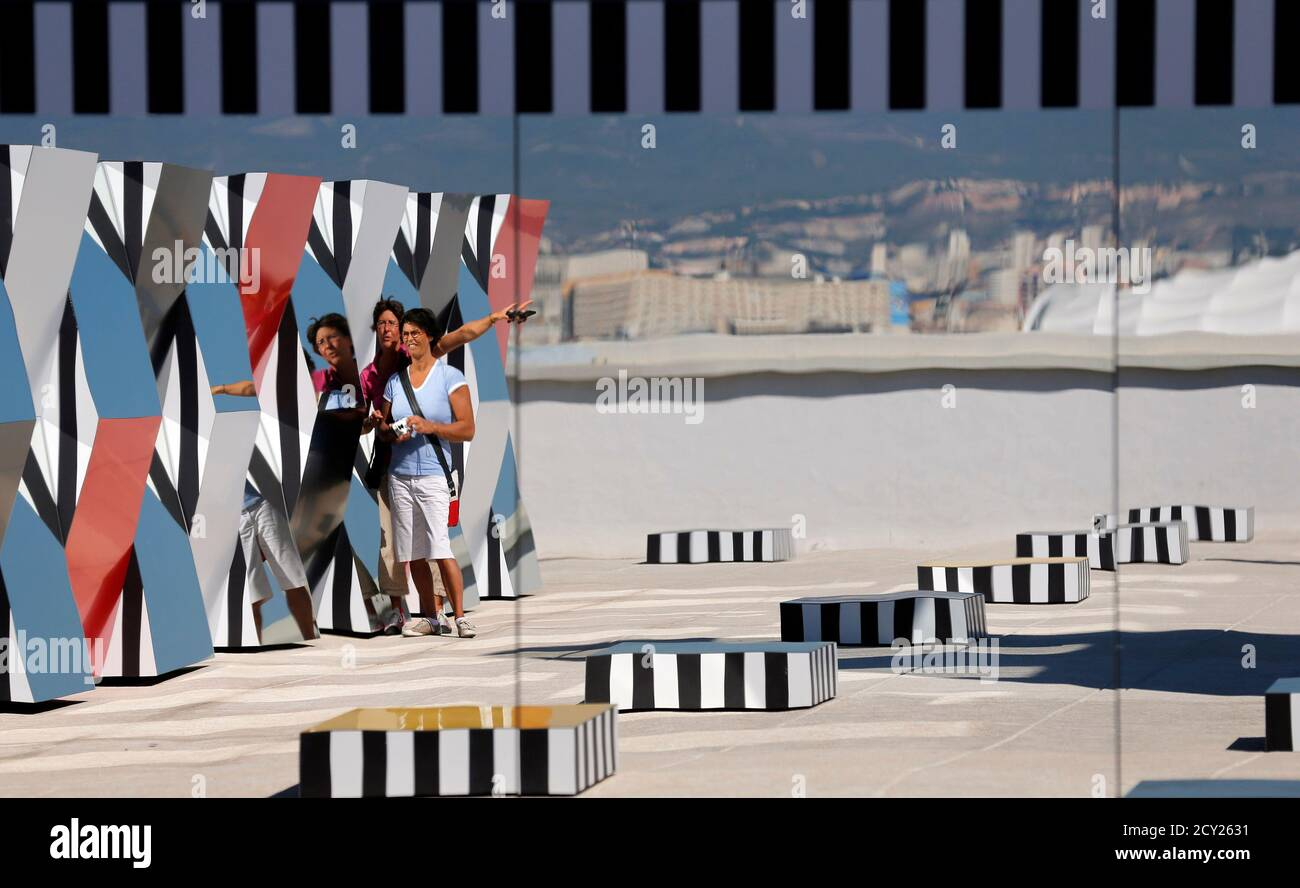 """Visitors are reflected in a creation as part of the exhibition """"Defini Fini Infini, Travaux in situ""""  by French artist Daniel Buren at the MaMo art center in Marseille September 12, 2014. The MaMo contemporary art center is installed on the restored rooftop terrace of Le Corbusier's 1947 Cite Radieuse (Radiant City) and created by French designer Ora-Ito. The exhibition will run until September 30, 2014.           REUTERS/Jean-Paul Pelissier (FRANCE  - Tags: ENTERTAINMENT SOCIETY) Foto de stock"""