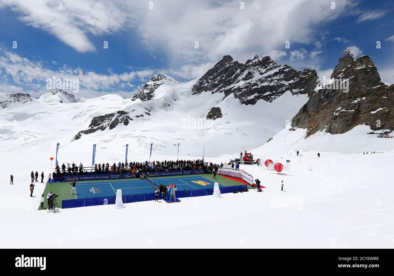 El tenista suizo Roger Federer (L) sirve una pelota al esquiador estadounidense Lindsey Vonn durante un evento promocional de tenis en el glaciar Aletsch en el Jungfraujoch el 16 de julio de 2014. El número tres del mundo y el campeón de esquí alpino jugaron en una pista de tenis especialmente preparada en un glaciar a una altitud de 3475 m (11401 pies). REUTERS/DENIS BALIBOUSE (SUIZA - TAGS: SOCIEDAD DEPORTE TENIS ESQUÍ TPX IMÁGENES DEL DÍA) Foto de stock
