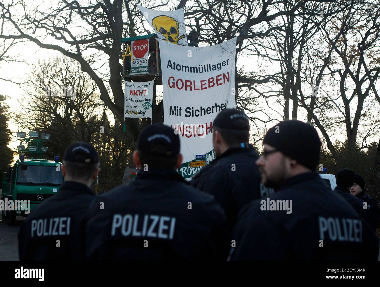 """An activist from the environmental organization Robin Wood observes the police from his tree house in Langendorf near Gorleben November 28, 2011. The controversial shipment of 11 Castor containers with spent German nuclear fuel reprocessed in France, will be loaded onto trucks in Dannenberg before its final transportation to the nearby intermediate storage facility in the northern Germany village of Gorleben. The banner reads: """"Radioactive waste storage Gorleben is not safe"""". REUTERS/Alex Domanski (GERMANY - Tags: ENVIRONMENT POLITICS CIVIL UNREST) Foto de stock"""