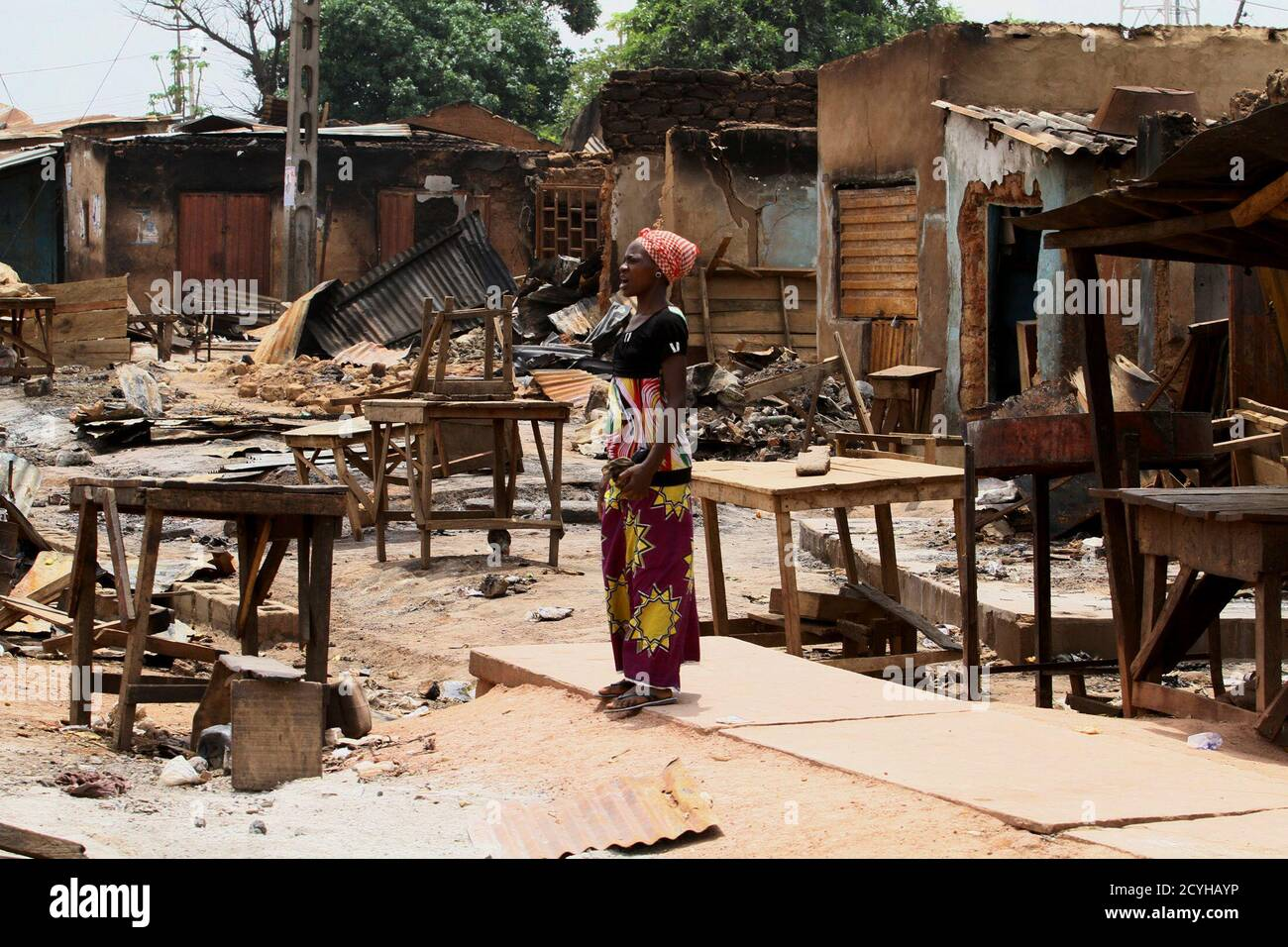 A woman stands in front of burnt buildings in Kachia village, where violence erupted last week, in Nigeria's northern state of Kaduna April 28, 2011. Voters trickled out to polling stations on Thursday in two states in northern Nigeria where rioting killed hundreds last week, under the watchful eye of policemen on horseback and soldiers manning barricades. REUTERS/Afolabi Sotunde (NIGERIA - Tags: CIVIL UNREST ELECTIONS POLITICS) Foto de stock