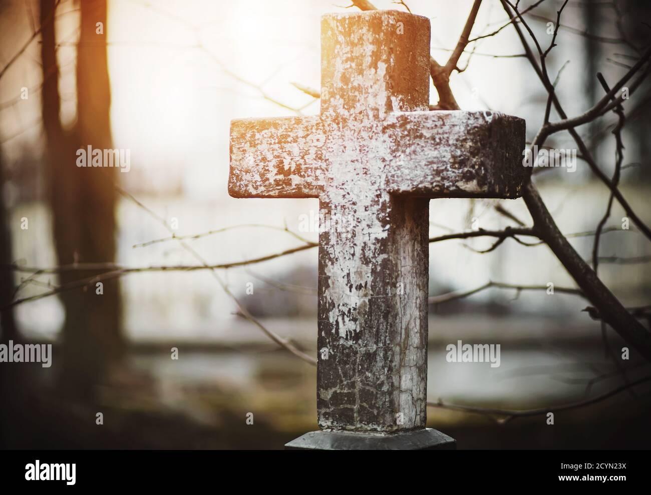 Una vieja y vieja cruz en el cementerio cerca de las ramas retorcidas está iluminada por los rayos del sol poniente. Religión. Muerte. Foto de stock