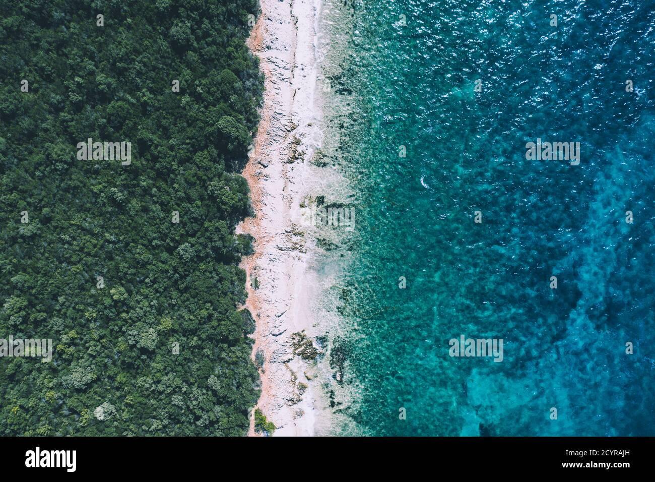 Concepto creativo de playa mínima. Distribución de vacaciones de verano con agua azul y arena sobre fondo brillante. Lay plano. Foto de stock