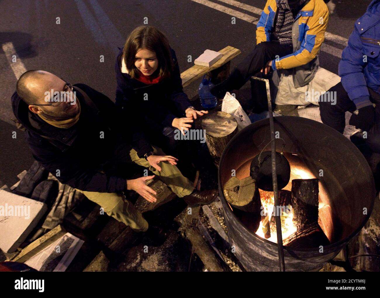Igor Skliarevsky and his wife Elena warm themselves at a fire in a pro-European protesters camp at Independence Square in Kiev, December 16, 2013. By day, Igor Skliarevsky works as a graphic designer. By night, he is an anti-government protester, sometimes manning the barricades in Ukraine's snowy capital. The 36-year-old delivers maps for fellow protesters, directing them to medical posts or kitchens. He also set up a website coordinating food, warm clothing and other supplies for those camped out on Kiev's Independence Square. Picture taken December 16, 2013.  REUTERS/Vasily Fedosenko (UKRAI Foto de stock