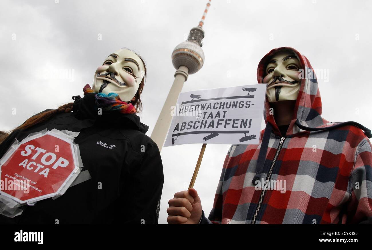 Protestors wearing Guy Fawkes masks participate in a demonstration next to the television tower against the Anti-Counterfeiting Trade Agreement (ACTA) in Berlin February 25, 2012. Protesters fear that ACTA, which aims to cut trademark theft and other online piracy, will curtail freedom of expression, curb their freedom to download movies and music for free and encourage Internet surveillance. The banner reads: 'Surveillance Society.' REUTERS/Tobias Schwarz (GERMANY  - Tags: POLITICS) Foto de stock