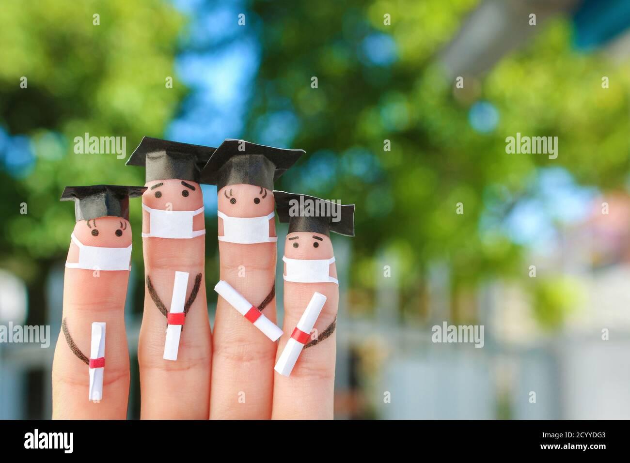 Arte de los dedos de los estudiantes en máscara médica de COVID-2019. Graduados que tienen su diploma después de graduarse. Foto de stock