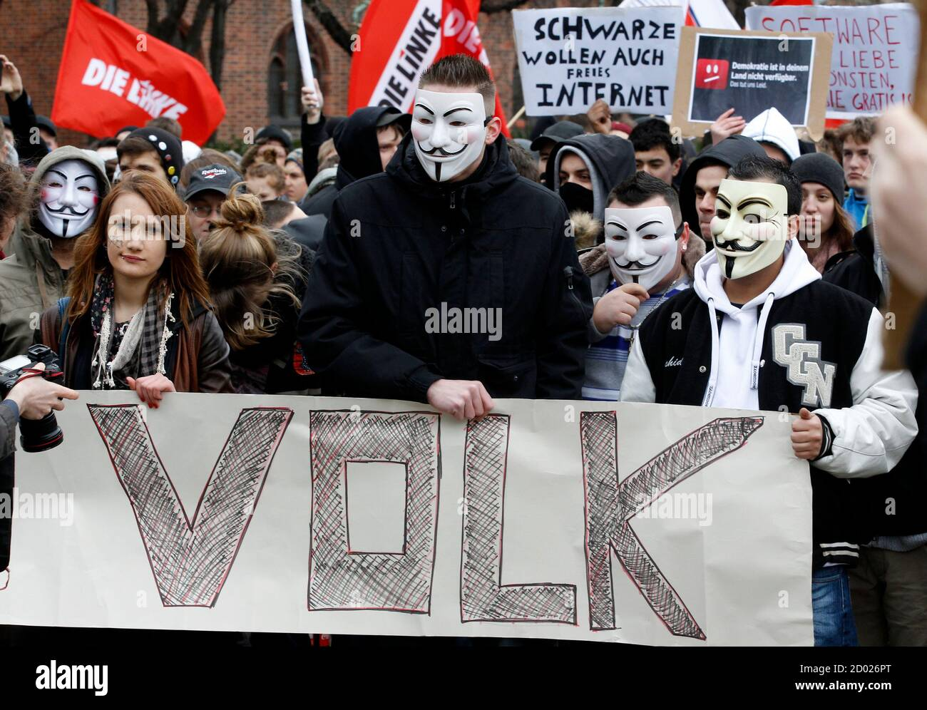 """Protestors wearing Guy Fawkes masks participate in a demonstration against the Anti-Counterfeiting Trade Agreement (ACTA) in Berlin February 25, 2012. Protesters fear that ACTA, which aims to cut trademark theft and other online piracy, will curtail freedom of expression, curb their freedom to download movies and music for free and encourage Internet surveillance. The banner reads """"People"""". REUTERS/Tobias Schwarz (GERMANY - Tags: POLITICS CIVIL UNREST) Foto de stock"""