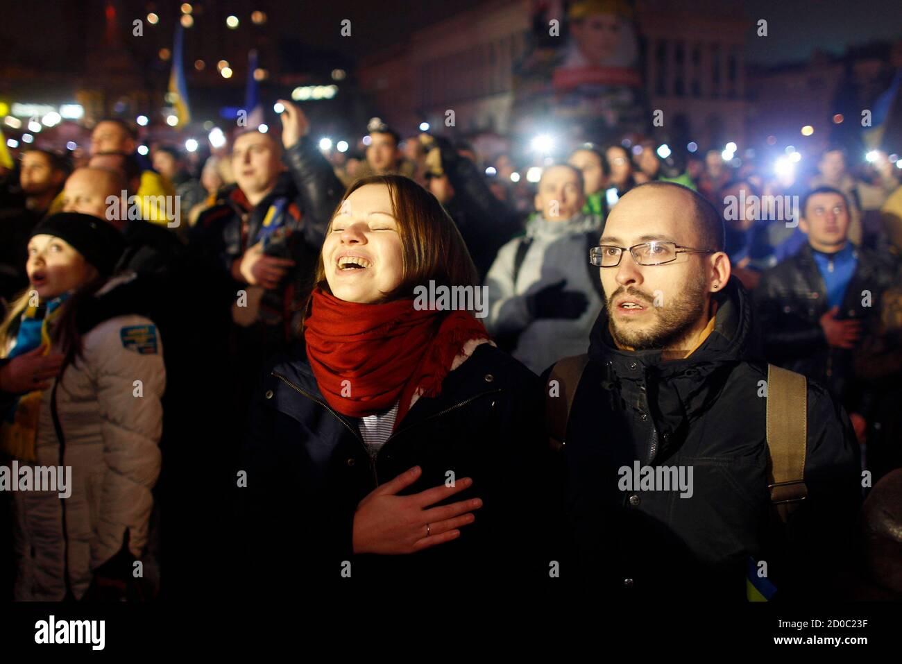 Igor Skliarevsky y su esposa Elena cantan el himno nacional durante una reunión pro-europea en la Plaza de la Independencia en Kiev, el 17 de diciembre de 2013. De día, Igor Skliarevsky trabaja como diseñador gráfico. Por la noche, es un manifestante anti-gubernamental, a veces manejando las barricadas en la capital nevada de Ucrania. El joven de 36 años entrega mapas para los compañeros manifestantes, dirigiéndolos a puestos médicos o cocinas. También creó un sitio web que coordinaba alimentos, ropa de abrigo y otros suministros para los acampados en la Plaza de la Independencia de Kiev. Foto tomada el 17 de diciembre de 2013. REUTERS/Vasily Fedosenko (UCRANIA - Foto de stock