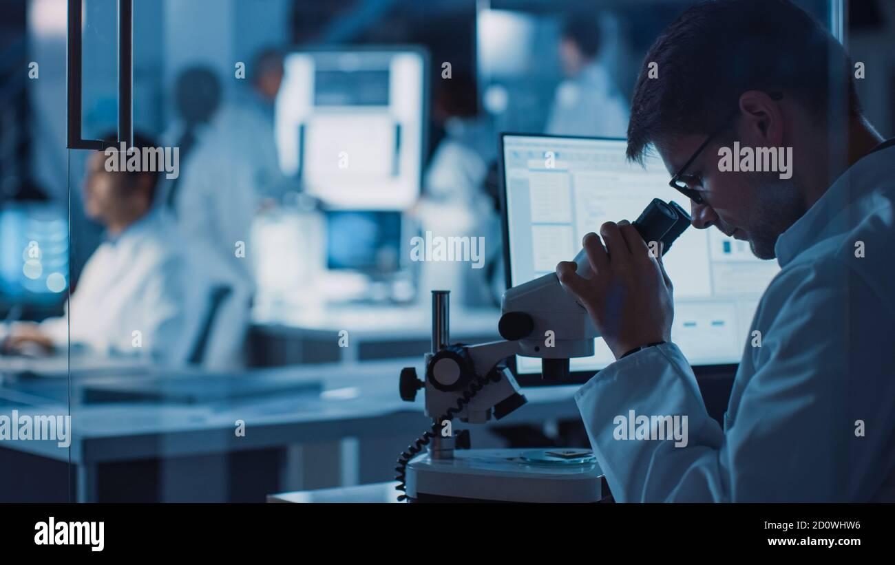 En el Laboratorio de Investigación Tecnológica: Equipo diverso de científicos Industriales, Ingenieros, Desarrolladores se reúnen alrededor de la Mesa iluminada e inspeccionan Blueprints Foto de stock