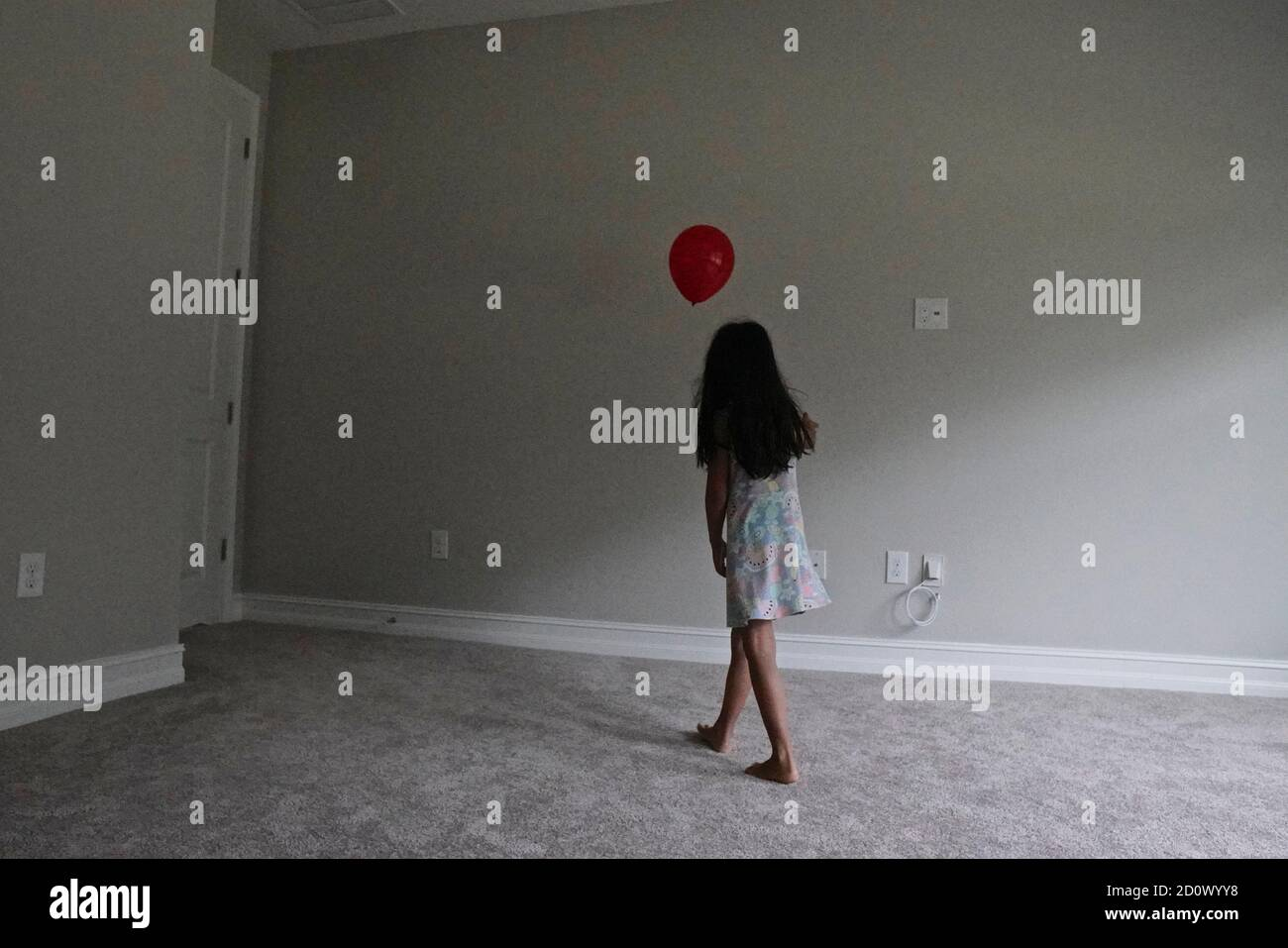Niña de cinco años jugando con un globo rojo una habitación vacía Foto de stock