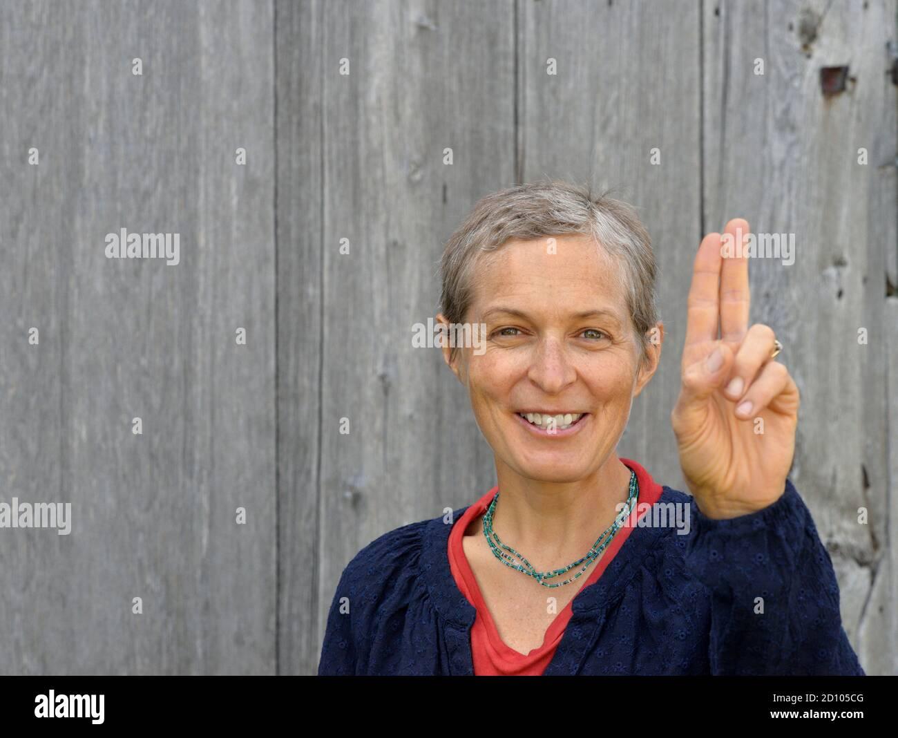 Mujer caucásica positiva de mediana edad con pelo corto (homesteader) hace un juramento con dos dedos, frente a un antiguo fondo de madera de granero. Foto de stock