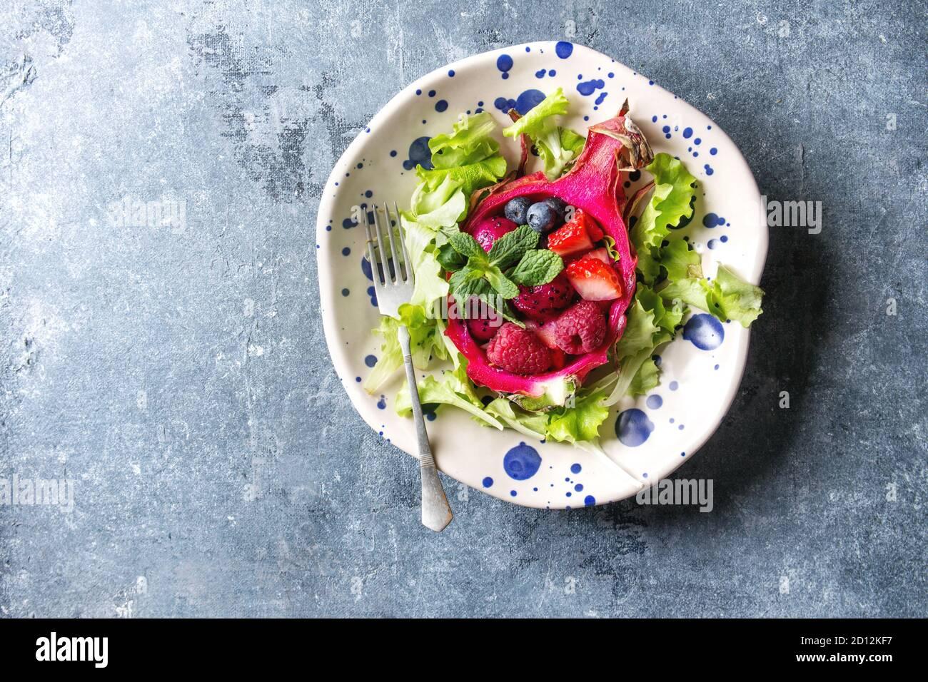 Ensalada de frutas veganas con bayas, ensalada verde y menta servida en fruta de dragón rosa en placa de cerámica manchada sobre fondo de textura azul. Vista superior, copiar Foto de stock