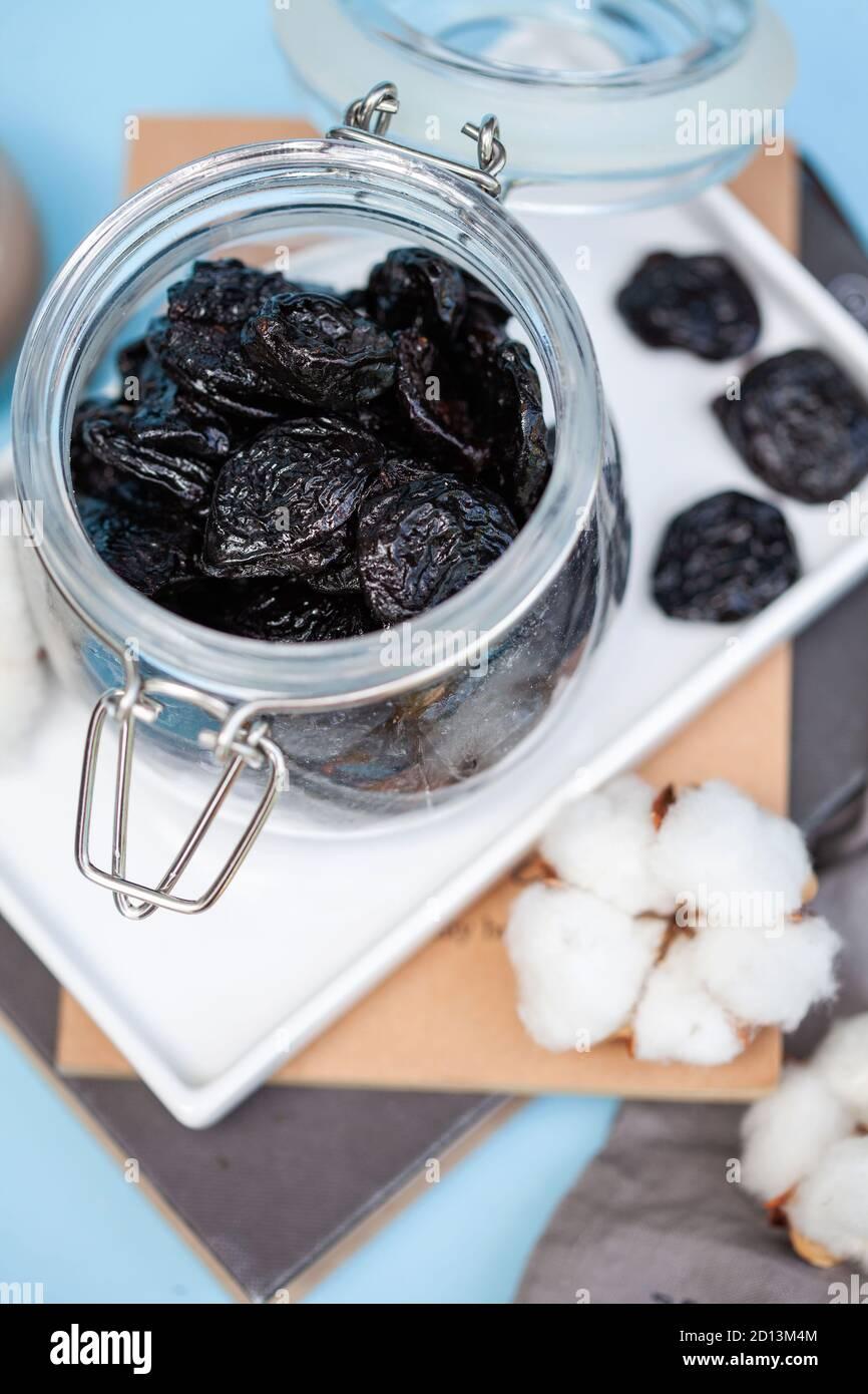 Un puñado de ciruelas pasas en un tarro de cristal sobre un soporte blanco sobre un fondo azul. Foto de comida. Foto de stock